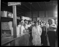 Unidentified men and women stand in line to receive food at a county food exchange program, Los Angeles, 1930s