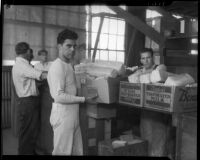 Unidentified men move boxes of food at a county food exchange program, Los Angeles, 1930s