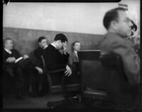 Louis Payne sits and bows head in a courtroom, Los Angeles, June-July, 1934