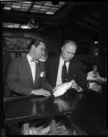 Judge William R. McKay stands with Wilson Atkins at a bar while cleaning a glass, Los Angeles, 1930s