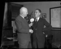 Supervisors John Anson Ford and Harry M. Baine shake hands and exchange a flower, Los Angeles, 1930s