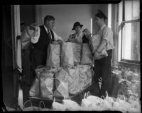 Law enforcement officials George Fisher, Elizabeth Fiske, and J.W. Buckley surrounded by bags of food, Los Angeles, circa 1930