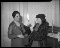 Actress Gloria Swanson and Minnie Barton burn the mortgage to the Bide-A-Wee home for working mothers, Los Angeles, 1935