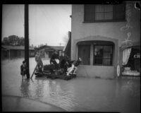 Children ride wooden raft across flood waters in Long Beach, 1930s