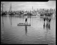 Unindentified men stand and float on a wooden raft in Long Beach flood waters, circa 1930s