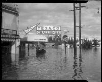 Three men ride a boat across flood waters, Long Beach, circa 1930s