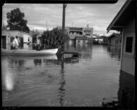 Unidentified men ride boat in flood waters near submerged vehicle and homes, Long Beach, 1930s