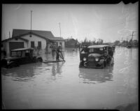 Children ride raft and a group of unidentified people surround a submerged vehicle in flood waters, Long Beach, 1930s