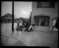 Adults and children ride on wooden raft in flood waters, Long Beach, 1930s