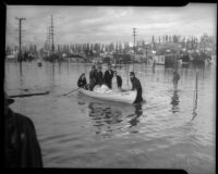 Unidentified men and women carry belongings and pets across flood waters, Long Beach, circa 1930s