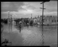 Children play and ride bicycles in flood waters, Long Beach, circa 1930s