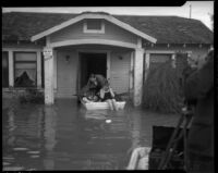 Unidentified man and woman in a boat outside a flooded home, Long Beach, circa 1930s