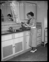 Jean Wilson uses a hand mixer in a kitchen, Los Angeles, 1930s