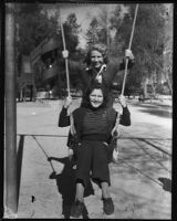 Two unidentifed women play on a swing set during the annual Iowa Picnic, Los Angeles, 1930s