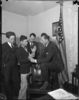Detective Lieutenant Ray Giese, Los Angeles County District Attorney Buron Fitts, and two unidentified men examine the hands of Thomas Edward Dugger who was on trial for assaulting three women, Los Angeles, 1935-1936