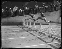 Jesse Owens competes in a hurdle race against an unidentified member of the USC track team, Los Angeles, 1935