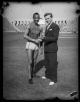 Jesse Owens shakes hand with unidentified spokesperson for USC, Los Angeles, 1935
