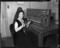 Mrs. Elaine Anderson Dudley poses next to a switchboard, Los Angeles, 1934