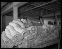 Rosalind Roennburg poses on a pile of mattresses at a factory, Los Angeles, 1935