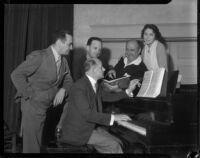 Group of people gather around a piano at a La Boheme performance at the Shrine Auditorium, Los Angeles, 1935