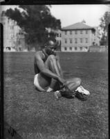Jesse Owens puts on running shoes while sitting on grass, Los Angeles, 1930s