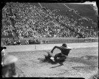 Jesse Owens lands a jump during a track meet, Los Angeles, 1930s