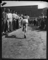 Jesse Owens sprints through a crowd of spectators, Los Angeles, 1930s