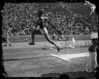 Jesse Owens competes in a broad jump event at a track meet, Los Angeles, 1930s