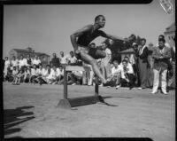 Jesse Owens jumps over a hurdle while spectators watch from the sideline, Los Angeles, 1930s