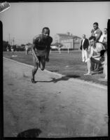 Jesse Owens sprints in front of a few spectators, Los Angeles, 1930s