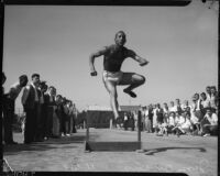 Jesse Owens jumps over a hurdle while spectators watch from the sidelines, Los Angeles, 1930s