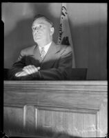 Board of Education member Stewart O. Mertz sits behind a podium, Los Angeles, 1935