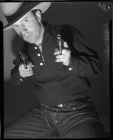 Dr. Ralph Wagner poses with two pistols while wearing a hat, Los Angeles, 1930s