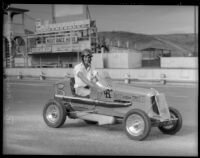 "Race car driver Rex Mays poses in a ""midget"" car at the Legion Ascot speedway, Los Angeles, 1935"