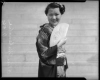 Miss Lil Tokio winner Alice Watanabe poses with a fan in a traditional kimono in honor of the Nsei festival, Los Angeles, 1935