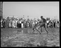 Mud covered students in wheelbarrow race at Los Angeles Junior College, February 1936