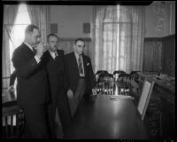 Lawyer Erwin P. Werner and Deputy Sheriff Contreras look at dart game exhibit during trial, October 1935