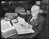 Thomas W. Robinson surrounded by books, unknown date