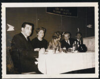 Aldous and Laura Huxley seated at table with unidenitified people [descriptive]