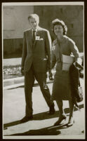 Aldous and Laura Huxley, walking outside in sunlight, dressed in suits [descriptive]