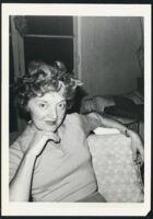 Laura Huxley seated, hand to chin [descriptive]