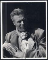 Aldous Huxley portrait, leaning on elbow, hands clasped, scarf around neck [descriptive]