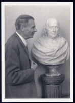Aldous Huxley with a bust of Benjamin Franklin [descriptive]