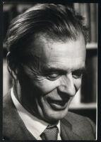 Aldous Huxley portrait, looking down, smiling [descriptive]