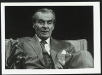 Aldous Huxley, seated in chair and gesturing hands, black background (1), identical image [descriptive]
