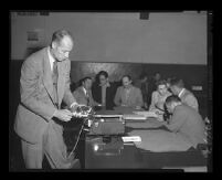Roger Otis demonstrates a recording device at the trial of Jack Santo, Emmett Perkins, and Barbara Graham, Los Angeles, 1953