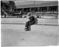 Spectator reads the paper at the Santa Anita racetrack, February 22, 1937.