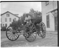 "J.H. Ozmun pictured in his Model 3 Holsman ""Highwheeler"" car after a cross-country trip, February 16, 1936."