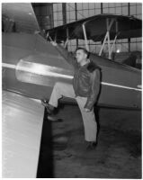 Paul Mantz, motion picture stunt pilot and consultant, poses with airplane.  Circa February 1936.