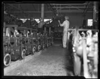 Men at work amid a line of car engines at the Los Angeles Studebaker assembly plant in Vernon, CA.  Circa January 2, 1936.